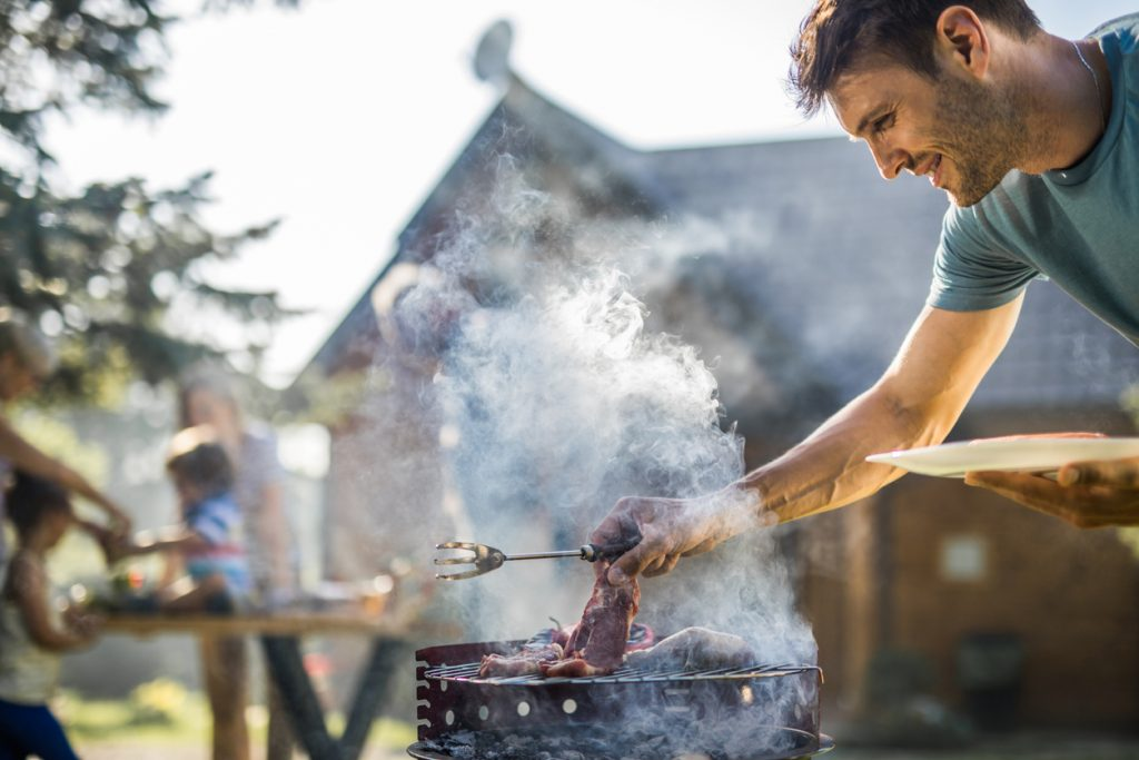 Happy man grilling meat on a barbecue grill outdoors.
